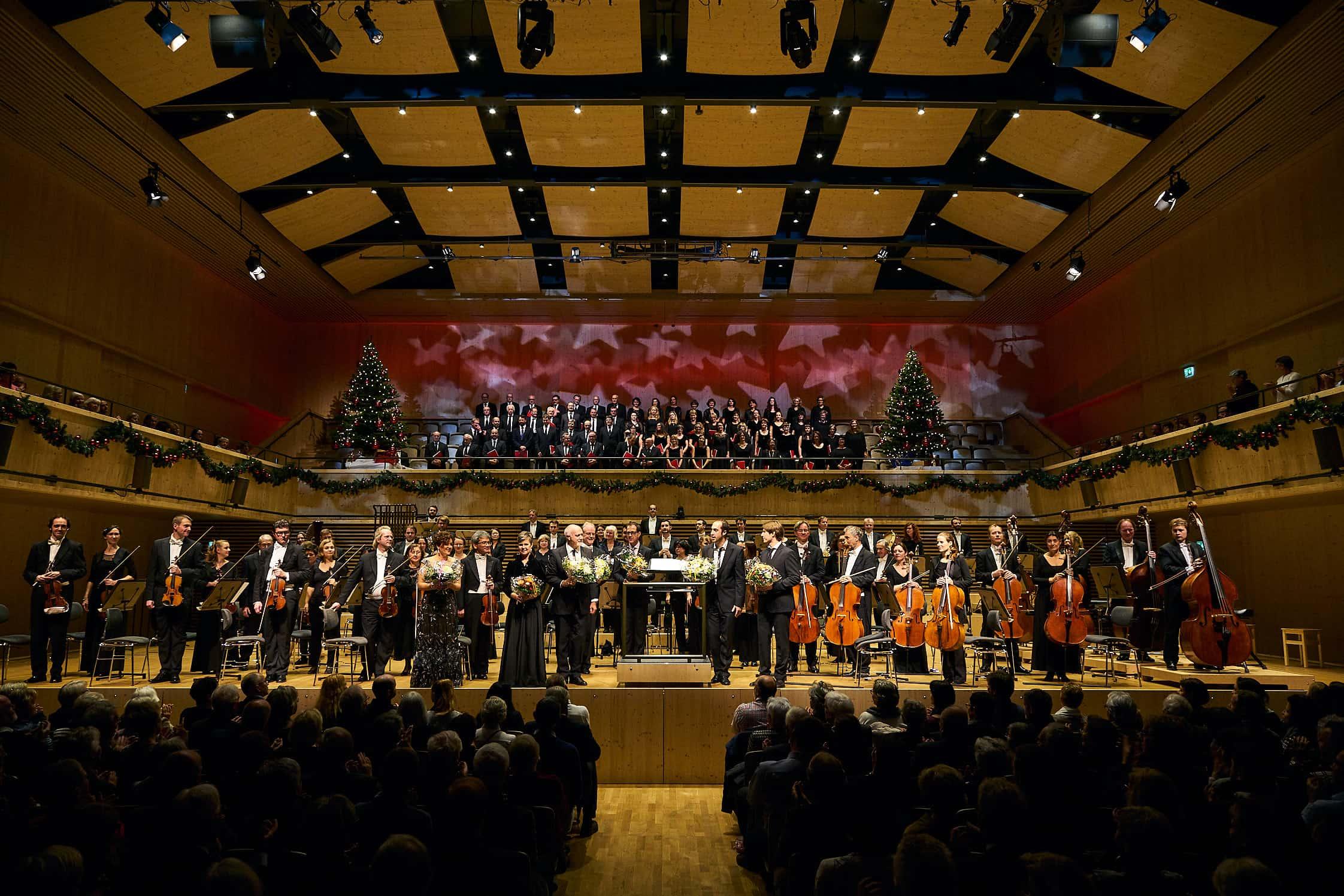 die Solisten und das gesamte Orchester empfängt stehend auf der Bühne den Schlussapplaus des Weihnachtskonzertes in der festlich geschmückten Tonhalle Maag in Zürich, die ganz aus Holz gebaut wurde.