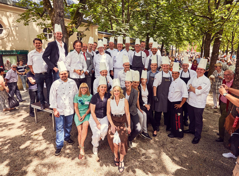 Eine große Gruppe von Köchinnen, Köchen und sonstigen Aktiven formiert sich mit Köchmützen zum Gruppenfoto und lachen in die Kamera.